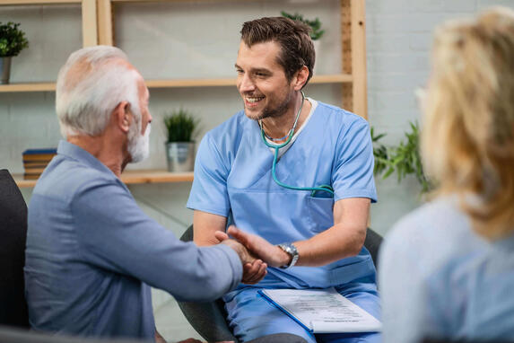 Happy-healthcare-worker-and-mature-patient-handshaking-during-a-home-visit.-1152840546_6720x4480
